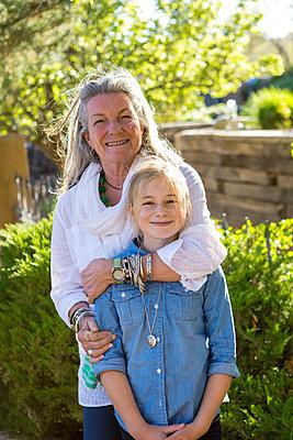 Smiling Caucasian grandmother hugging granddaughter - p555m1304158 by Marc Romanelli