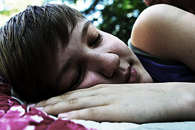 Young woman sleeping in a garden - p7030045 by Anna Stumpf