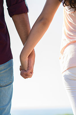 Close up of a young man and woman holding hands outdoors  - p794m1510970 by Mohamad Itani