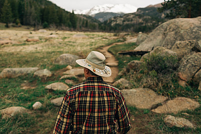 A retired man walks along a trail in Rocky Mountain National Park, CO. - p1166m2147237 by Cavan Images