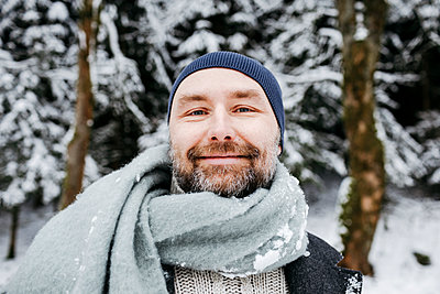 Smiling mature man wearing scarf on snow during vacations - p300m2256415 by Katharina Mikhrin