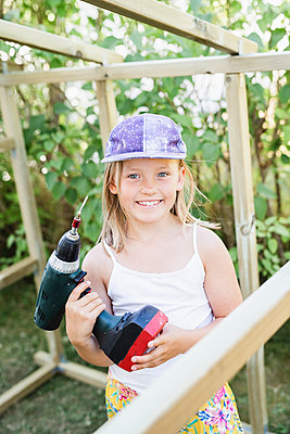 Smiling girl with electric drill - p312m2091636 by Anna Johnsson
