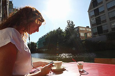 Woman in headphones having coffee - p429m743823 by Daniel Allan