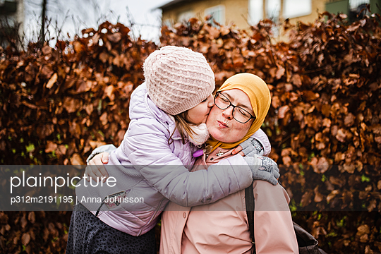 Mother with daughter hugging - p312m2191195 by Anna Johnsson