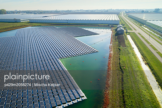 Floating solar panels installed on water supply of neighbouring greenhouses, elevated view, Netherlands - p429m2058274 by Mischa Keijser