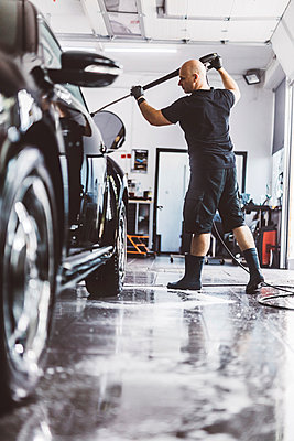 Rear view of male worker pouring water on car with hose in workshop - p1166m2060378 by Cavan Images