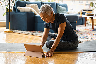 Senior woman exercising while learning through digital tablet - p1166m2285601 by Cavan Images