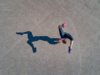 Aerial view of sportive young woman training handstand - p300m2005372 by Stefan Schurr