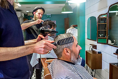 Male hairdresser using dryer while combing customer's hair at barber shop - p300m2240013 by LOUIS CHRISTIAN