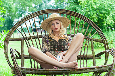 Blonde woman sitting in giant armchair - p427m1468138 by Ralf Mohr