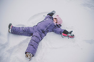 Young girl making snow angel in snow - p924m1547504 by Jenn Austin-Driver (Photography)