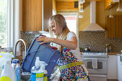 Young woman cleaning kitchen with green cleaning products - p924m973853f by heshphoto