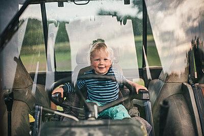 Kleiner Junge spielt auf einem Traktor - p1046m1220960 von Moritz Küstner