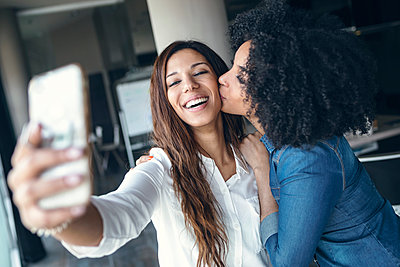 Smiling businesswoman taking selfie while being kissed by female colleague in office - p300m2275661 by Josep Suria