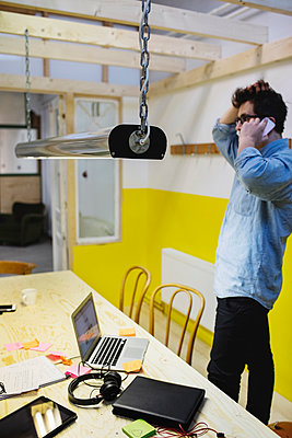 Side view of young man answering smart phone in creative office - p426m1407154 by Maskot