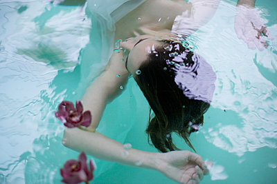 Woman underwater in spa swimming pool with orchids - p429m1174991 by Iveta Vaivode