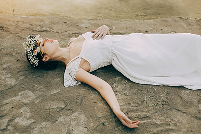 Caucasian bride laying on beach - p555m1303664 by Sophie Filippova