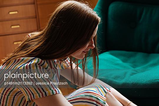 Frau sitzt auf Boden im Wohnzimmer - p1491m2173392 von Jessica Prautzsch