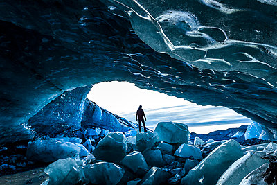 Rear view silhouette of person standing on ice rock at the entrance to a glacial ice cave. - p1100m1520318 by Mint Images
