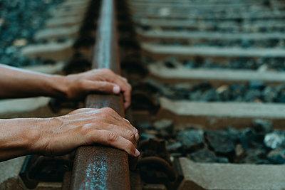 Man gripping the rusty rail of a railway track - p1423m2277929 by JUAN MOYANO