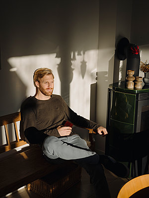 Man relaxing on bench at home - p300m2166617 by Kniel Synnatzschke