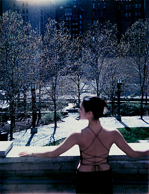 Woman in backless dress stands on balcony overlooking park - p3720830 by Andrew Thomas Hunt