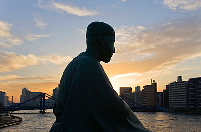 A statue of Matsuo Basho (Japan's most renowned haiku poet) overlooks the Sumida River and Kiyosubashi Bridge from the Basho-An Garden, located in the shitamachi downtown Koto-ku District of Tokyo, Japan. - p855m971971 by Ben Simmons