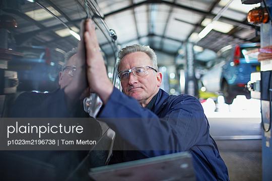 Male mechanic examining car in auto repair shop - p1023m2196738 by Tom Merton
