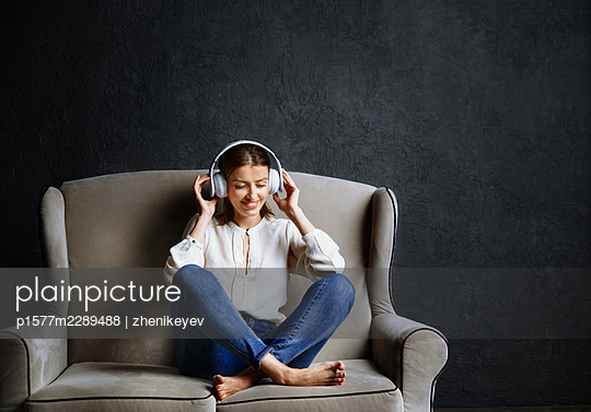 Beautiful woman wearing headphones and enjoying music - p1577m2289488 by zhenikeyev