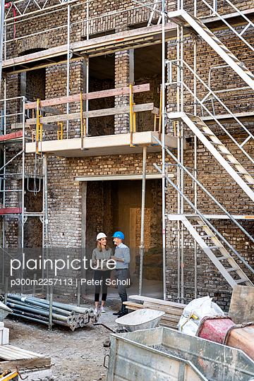 Businesswoman with digital tablet working with colleague at construction site - p300m2257113 by Peter Scholl