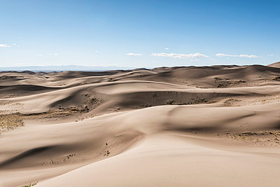 Scenic view of sand dunes against sky - p1166m1210630 by Cavan Images