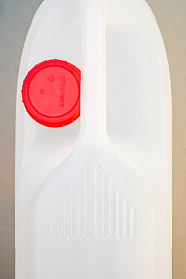 A white plastic milk bottle with a red plastic screw on cap looking like a monocle - p1302m2176754 von Richard Nixon