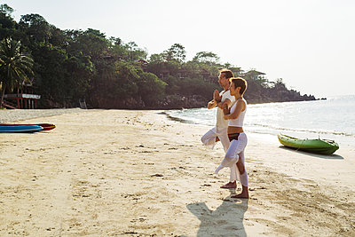 Thailand, Koh Phangan, couple doing yoga on a beach - p300m1568323 by Mosuno Media