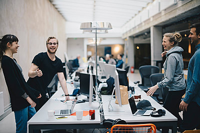 Happy computer programmers talking at desk in office - p426m1493889 by Maskot