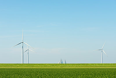Wind turbines in field landscape with ship sails on horizon - p429m1469555 by Mischa Keijser