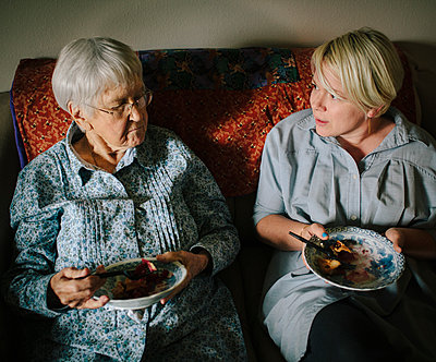 Older woman and granddaughter eating on sofa - p555m1408705 by Shestock