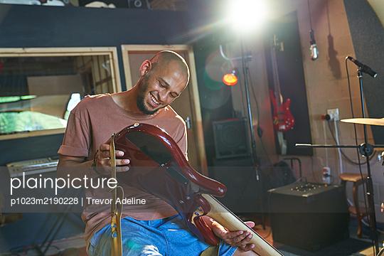 Smiling male musician inspecting guitar in recording studio - p1023m2190228 by Trevor Adeline