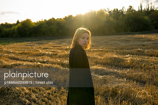 Young woman in stubble field in the evening sun - p1646m2249819 by Slava Chistyakov