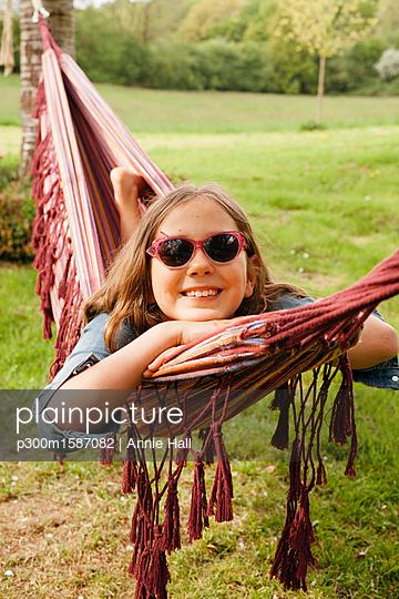 Portrait of smiling girl wearing sunglasses lying in hammock - p300m1587082 von Annie Hall