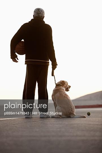 Black man holding basketball and walking dog
