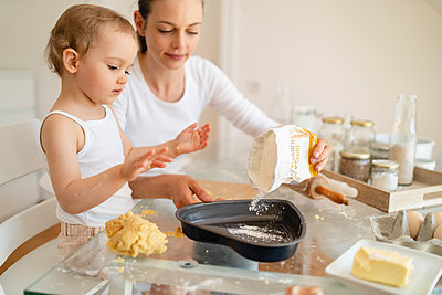 Mother and little daughter making a cake together in kitchen at home - p300m2102765 by Daniel Ingold