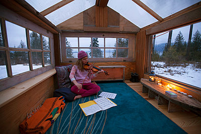 A Young Girl Practicing Her Violin In A Small Cabin Made Completely From Scrap Wood - p343m1218161 by Woods Wheatcroft