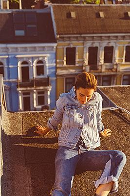 Frau sitzt entspannt auf Hausdach - p432m2203192 von mia takahara
