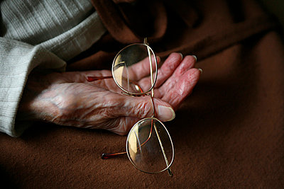 Glasses in the hand of a senior woman - p8960990 by Caro Bonink