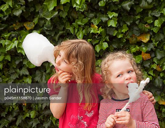 Zwei Freundinnen essen Zuckerwatte - p045m1158870 von Jasmin Sander