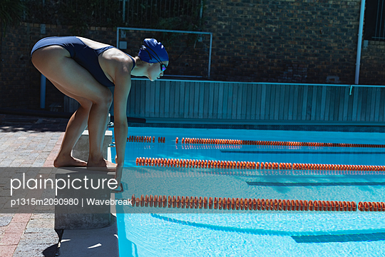 Young female swimmer standing on starting block in starting position - p1315m2090980 by Wavebreak