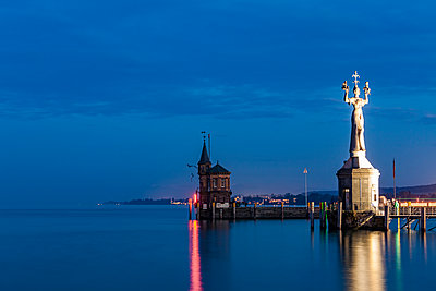 Germany, Constance, view to port entrance with lighthouse and Imperia at twilight - p300m1587754 by Werner Dieterich