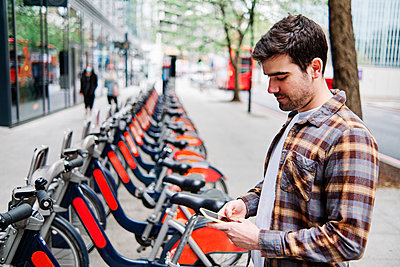 Man using mobile phone while standing at bicycle parking station - p300m2287313 by Angel Santana Garcia