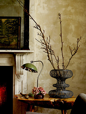 Branches in wire mesh vase with vintage table lamp at fireside - p349m2167825 by Polly Wreford