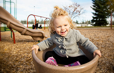 A cute young girl spinning in a saucer on a playground during the fall season; Spruce Grove, Alberta, Canada - p442m2004265 by LJM Photo